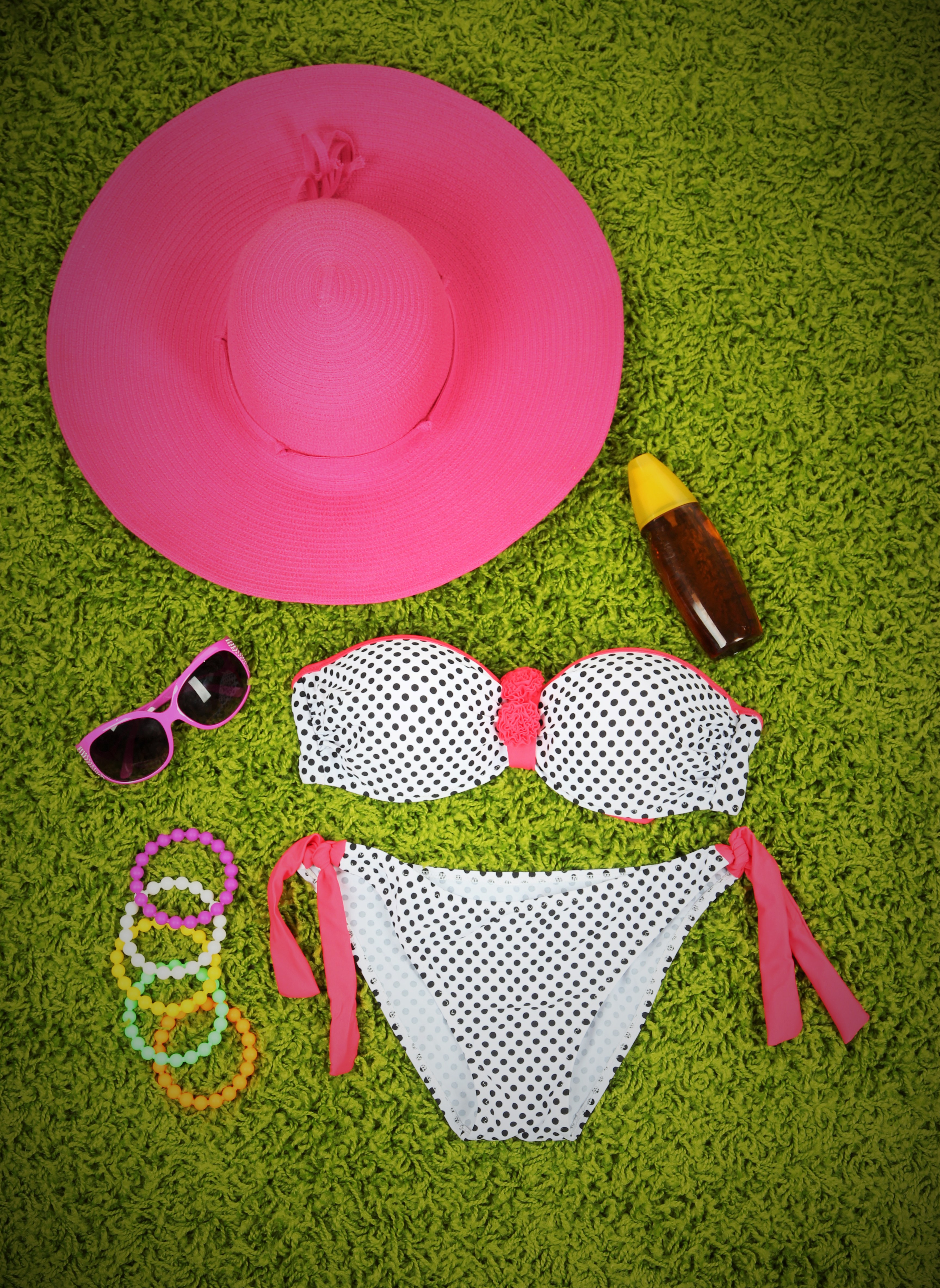 Swimsuit and beach items on green background